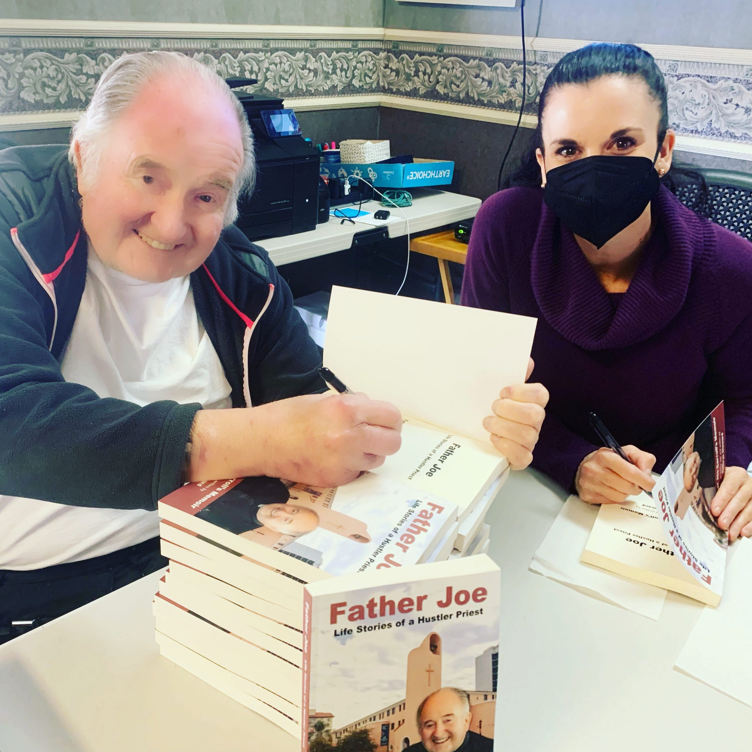Father Joe and Kathryn Cloward signing Father Joe Life Stories of a Hustler Priest